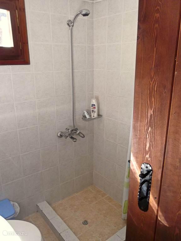 De douche met warm water uit een elektrische boiler.