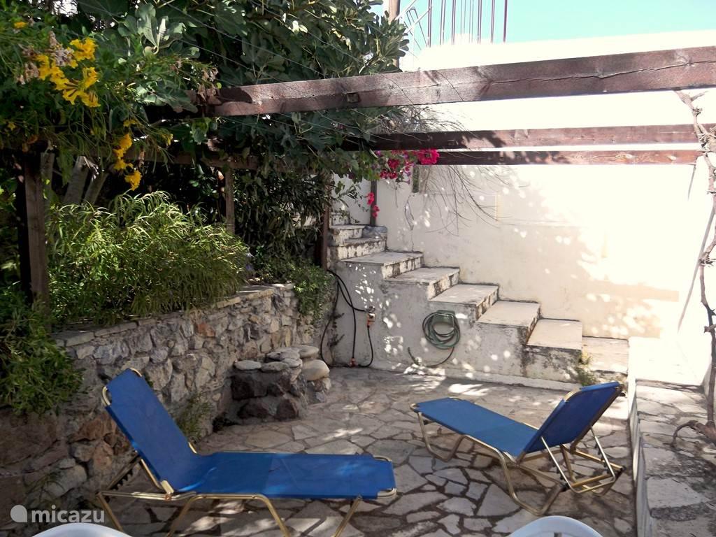 Het achterterras. Met op de achtergrond de openbare trap, die rechts langs het huis loopt en voert naar een hoger gelegen terras.