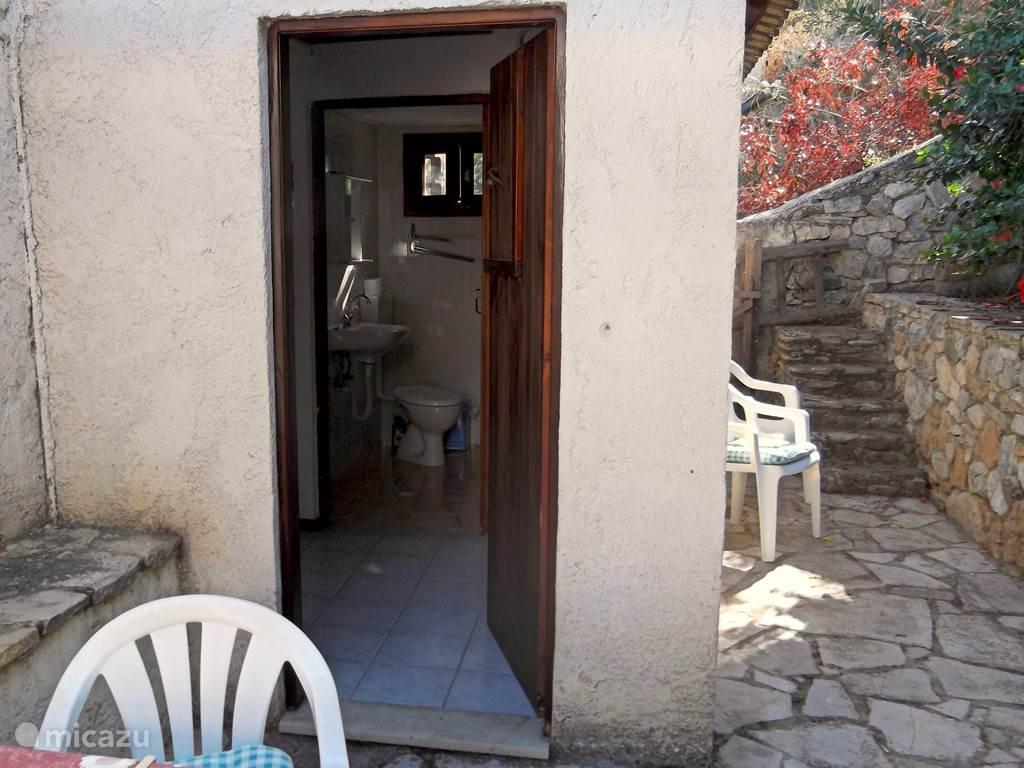 Het achterterras. De deur naar het achterhalletje en de badkamer.