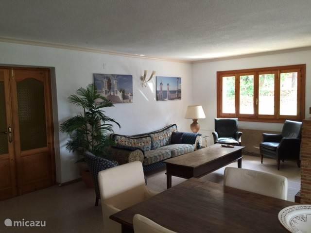 Woonkamer met openhaard, bureau, televisie en gezellige tafel voor 8 personen.