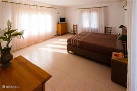 Slaapkamer  met airconditioning, drie terassen en aangrensende badkamer.