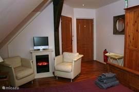 Slaapkamer (2) feer haard en twee lekkere kuip stoeltjes.