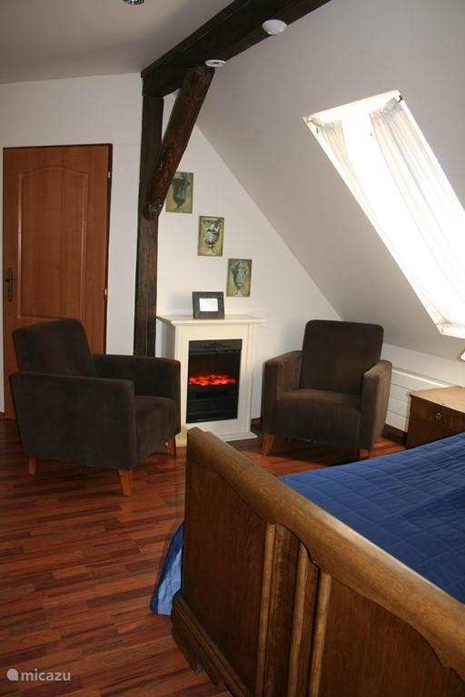 Slaapkamer 3 met sfeer haardje en lekkere stoelen.