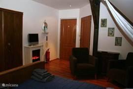 Slaapkamer (3)heeft twee relax stoelen en sfeer haardje.