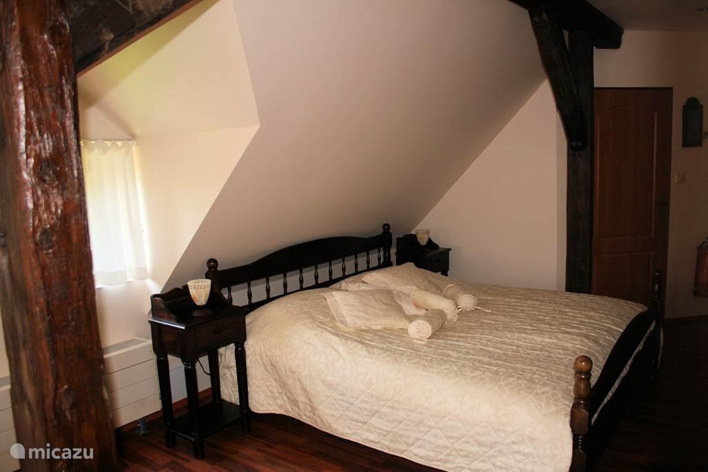 Slaapkamer (5)(extra optie) De Masterroom is koloniaal ingericht met een bed voorzien van verstelbare bodems.