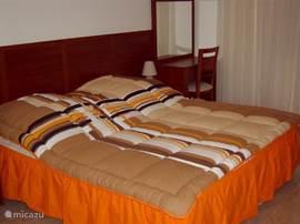 Master bedroom met nachtkastjes en een grote inbouwkast