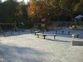 Hier de nieuw aangelegde  speeltuin. met bankjes zodat de ouders ook even kunnen zitten en een praatje kunnen maken. Deze speeltuin is voor bij de receptie, achter op het park is deze zomer vlakbij onze bungalow een nieuwe speeltuin aangelegd met klimwand kettingbrug een verschillende speeltoestell