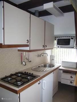 De keuken in de bungalow is een open keuken met alles wat u nodig heeft combioven koffieapparaat koelkast met vriesvakje enz.