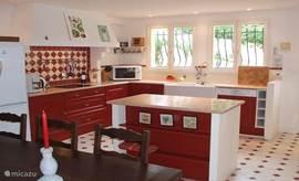 Binnenkeuken van alle gemakken voorzien met grote eettafel geschikt voor 12 personen.