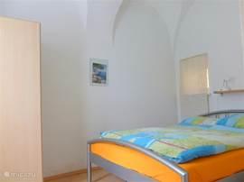 Slaapkamer met uniek gewelfd plafond en zicht op binnenhof