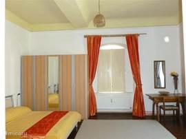 Ruime slaapkamers met uitzicht op tuin, hoge plafonds en authentieke klapluiken.