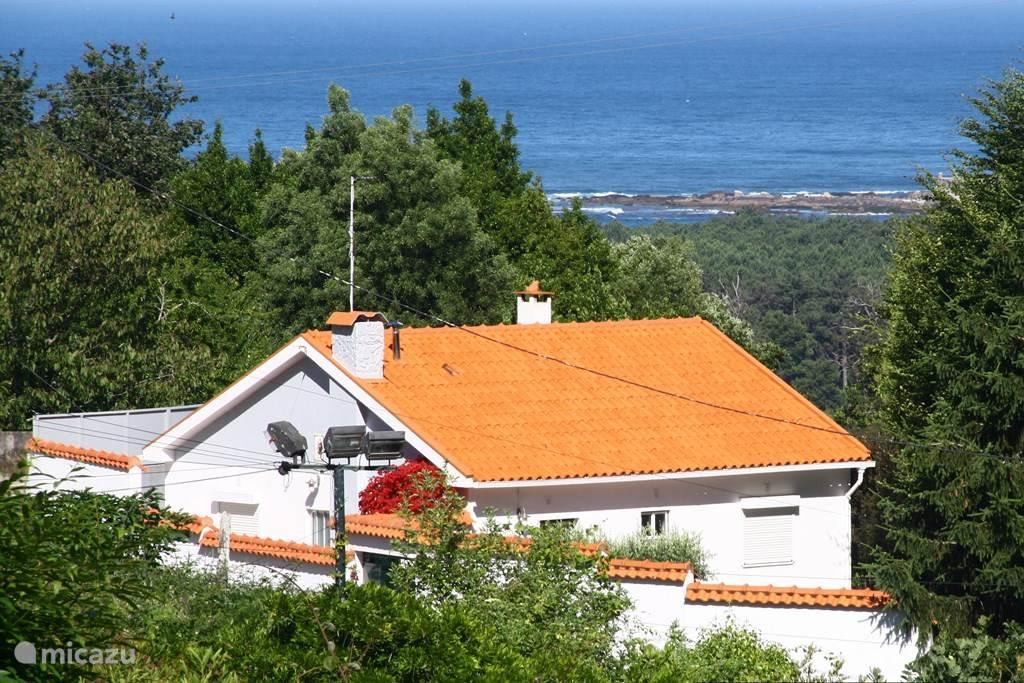 Indruk van de woning in het landschap, met het uitzicht op zee.