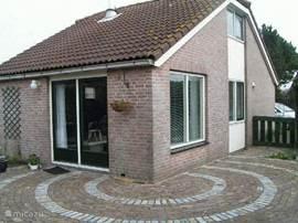 De bungalow gezien vanaf het terras. Via de openslaande deuren in de woonkamer stapt men direct in de tuin.