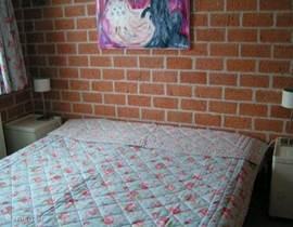 De tweepersoons slaapkamer met Auping bed op de begane grond