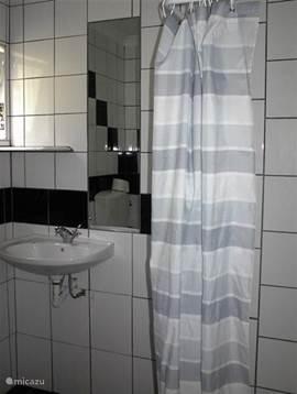 De badkamer met douche, wastafel en toilet. Het appartement heeft 2 badkamers.