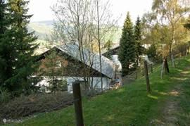 Dit is de woning bezien vanaf het wandelpad dat vlak boven de woning langs loopt en van waaruit u direct het bos in wandelt.