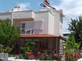 Voorzijde van de woning met grote Veranda en fraai aangelegde tuin met veel fruitbomen, zoals Perzik, Banaan, Citroen, Kers, Olijf en Sinaasappel. Prachtig uitzicht op de Egeïsche Zee en en het Griekse eiland Samos.