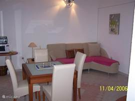 Entrance into the living room with dining table, which is extensible so that six people have place and corner sofa, which can be too. Possibly used as sofa