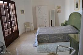 Ruime slaapkamer met dubbele open- slaande deuren naar het balkon. Eigen badkamer met ligbad, wc en bidet intern.