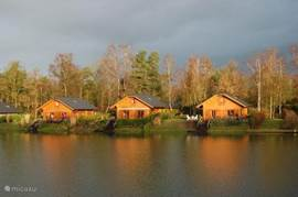 Uitzicht op de overkant van het meer vanuit de woonkamer en het houten terras