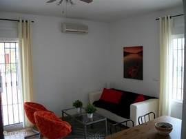 De gezellige woonkamer is ruim en licht, en voorzien van alle gemakken. Openslaande deuren naar de tuin, een keuken met alle benodigde apparatuur en achteruitgang.