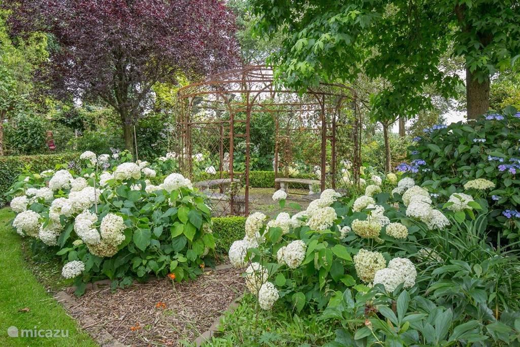 Een romantisch prieeltje in een prachtige, bloeiende tuin
