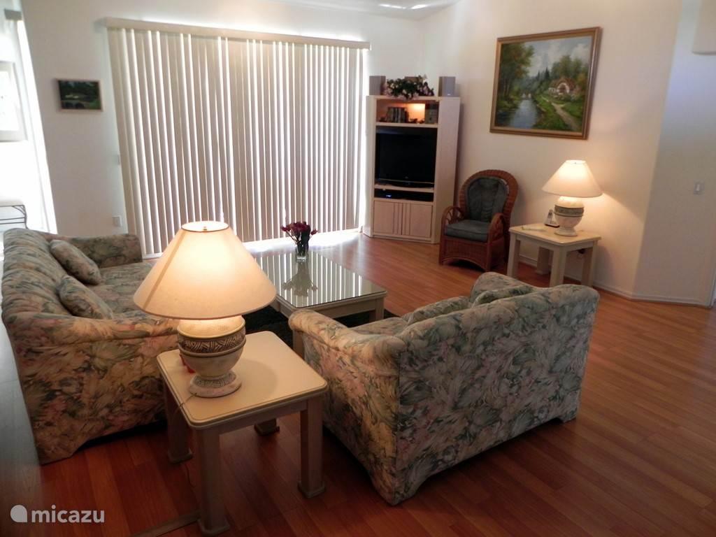 Huiselijke woonkamer met een gemakkelijke 3 en 2 seaters, groot LCD scherm en salontafel.