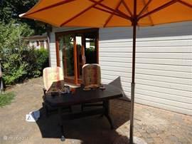 Het terras met tuinameublement met 4 stoelen en parasol. In het tuinhuisje staan nog extra stoelen. Tevens een stenen barbecue.