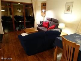 De woonkamer heeft twee tweezitsbanken en een stoel. Het grote raam kijkt uit op de tuin. Een TV en DVD speler zijn aanwezig.