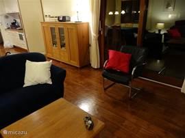 In de woonkamer zijn er grote tuindeuren naar het terras. Het dressoir bevat serviesgoed.