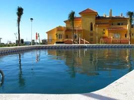 Een van de drie zwembaden van het complex met een van de gebouwen met ieder 13 appartementen. Er zijn 11 van deze gebouwen met ieder 13 appartementen.