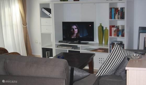 De living van het appartement met nederlandse televisie en airconditioning.-