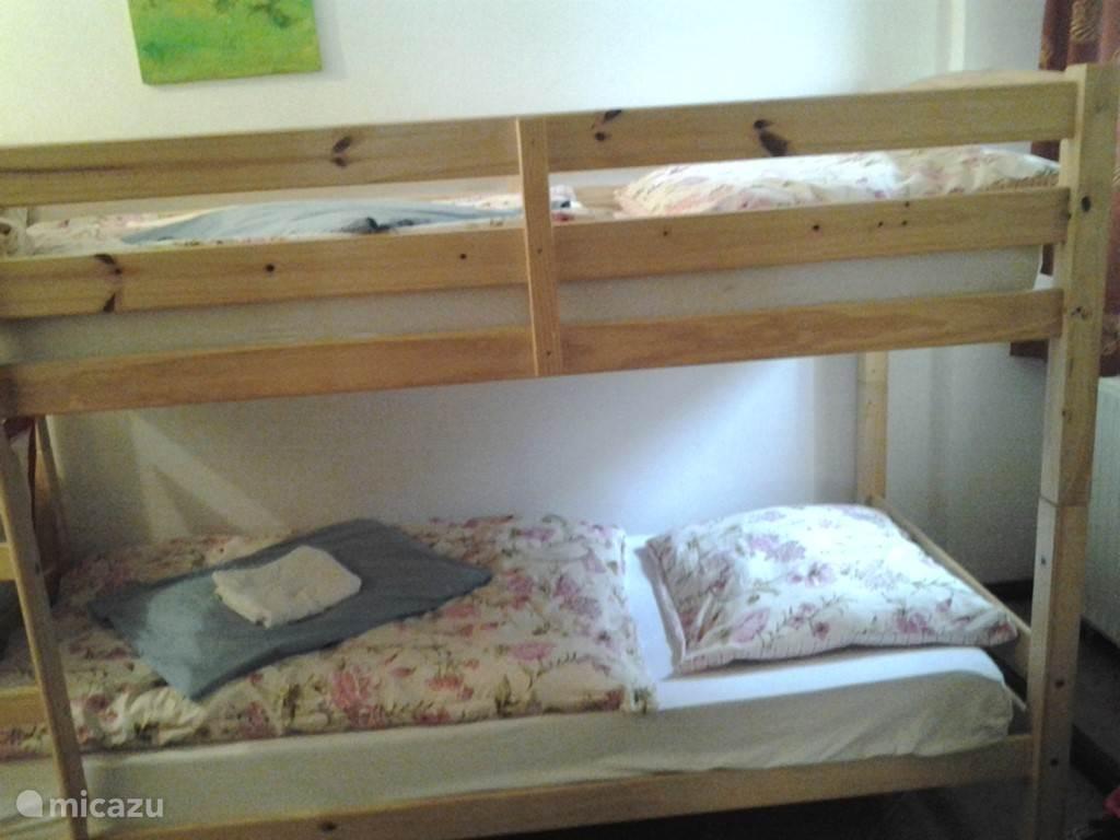 Aangrenzend aan de ouderslaapkamer ligt een kleine kamer met stapelbed en kinderhoekje.