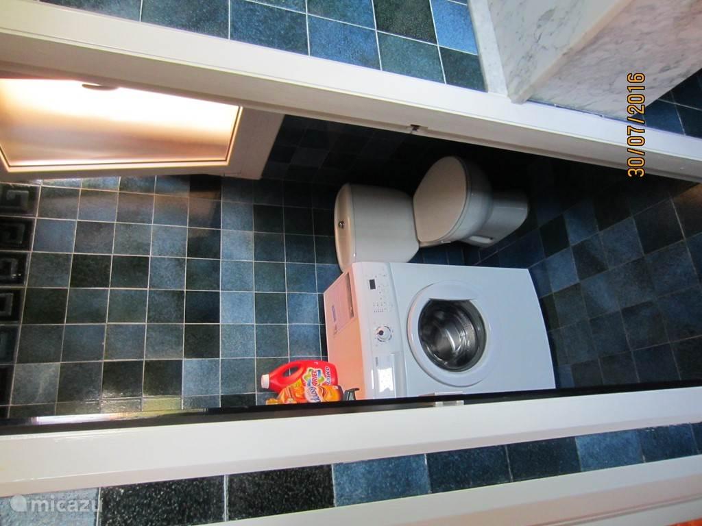 De w.c. en tevens de ruimte waar de wasmachine staat.