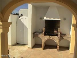 Buiten, naast de keuken en een overdekt terras, bevindt zich een vaste barbecuekeuken met aanrecht, wasbak en verlichte werkruimte