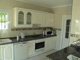 Grote moderne open keuken met zwart granieten aanrechtblad en alle apparatuur waaronder vaatwasmachine, magnetron, inbouwoven en amerikaanse koelkast met ijsblokjes en koudwater voorziening