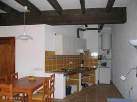 De open keuken met kookplaten, magnetron, koffiezetapparaat en waterkoker.