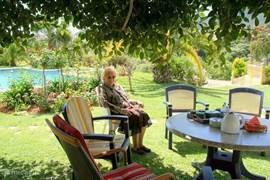 Ondanks dat de tuin volop in de zon ligt de hele dag ( ligging op het zuiden) is er ruim voldoende schaduwplek in de tuin. U hoeft uw stoelen alleen maar te verplaatsen.Dit is een foto van mijn moeder.Ook zij logeert regelmatig in het appartement. Bij voorkeur in het voorjaar.
