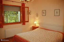 Benedenslaapkamer met een goed liggend lits-jumeaux bed waar vandaan u direct uw eigen ruime badkamer inloopt. In de zomermaanden blijft het koel doordat de kamer in de schaduw van een grote ficus-boom ligt. Voor de ramen zijn muggenhorren, rolluiken en gordijnen voor een ongestoorde nachtrust.