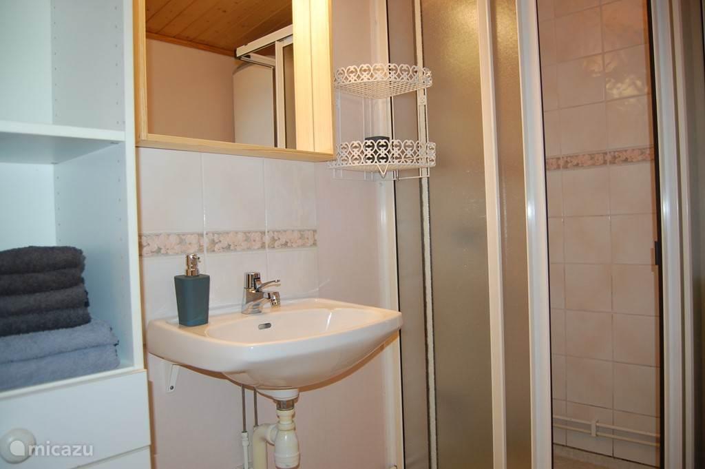 De badkamer, bij de entree gelegen, is praktisch ingedeeld met een wastafel, douche, wasmachine en wc. Handdoeken zijn inclusief.
