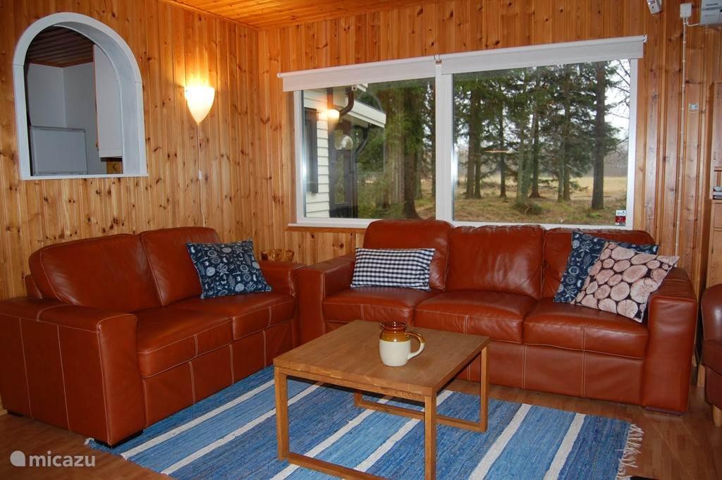 Knusse woonkamer met rondom uitzicht op het bos.