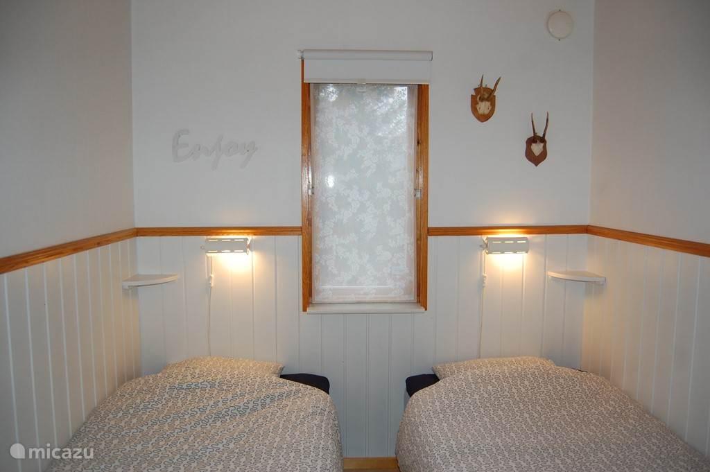 Knusse slaapkamer met twee enkele bedden en kast.