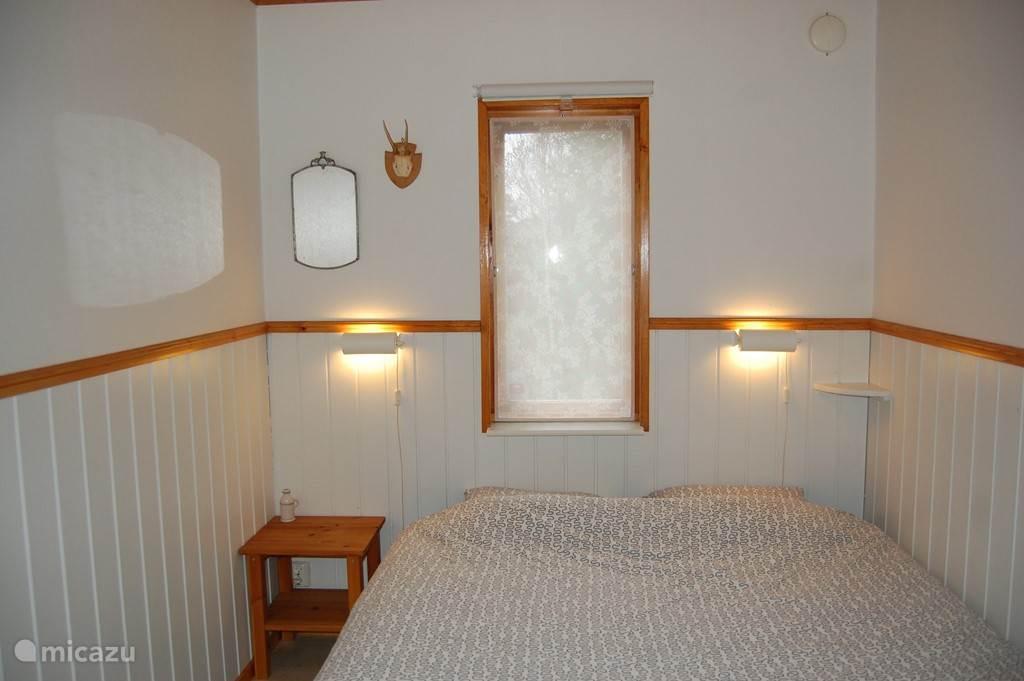 Knusse slaapkamer met tweepersoons bed en kast.
