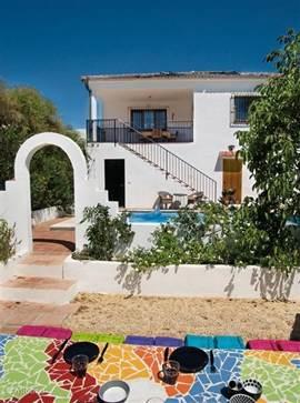 Casa Feliz vanuit de tuin met de mozaiektafel. U hoort alleen de krekels en de nachtegaal, de koekoek en hier en daar een blaffende hond, een paard of een geit, verder het ruisen van de wind en het zachtjes klotsende zwembadwater.