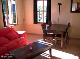 zonnige en gezellige huiskamer met houtkachel en cv.