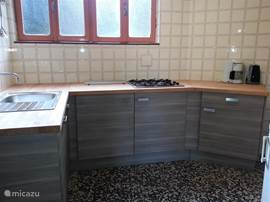 Ruime lichte keuken met koelkast en oventje en ruim werkblad. De ramen geven uitzicht op de tuin.