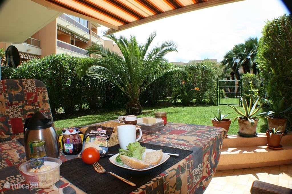 Ruim terras met breed elektrisch zonnescherm en zicht op eigen tuin en centrale palmentuin