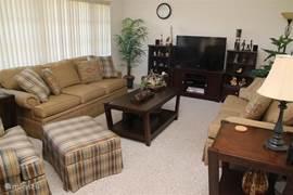 De familie kamer met een 46 inch LED TV met 5.1 surround sound systeem en Blu ray speler, een 2 en een 3 zits bank en een heerlijke fauteuil.