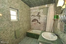 De ruime badkamer heeft bad met douche, wastafel en toilet.