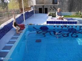 Een muur van het zwembad heeft ook een mozaiek: van inktvissen.